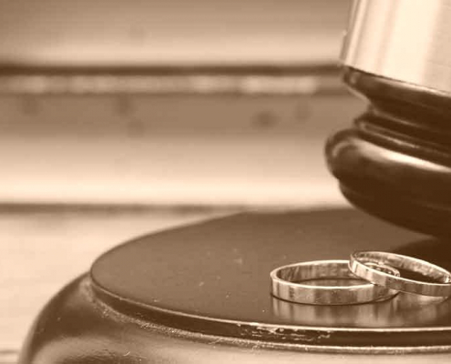 judges gavel next to two wedding rings